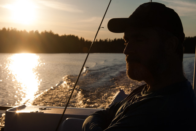 Lawrence sitting in a boat at sunset